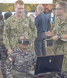 JOINT BASE PEARL HARBOR-HICKAM, Hawaii (June 29, 2018) Rim of the Pacific (RIMPAC) 2018 Innovation Fair visitor uses a virtual reality demonstration from the COMSUBPAC Innovation Lab booth, in Joint Base Pearl Harbor-Hickam. The innovation fair is to accelerate the delivery of innovative capabilities to operators by introducing and demonstrating the capability and technology in an operationally relevant environment. Twenty-five nations, more than 45 ships and submarines, about 200 aircraft and 25,000 personnel are participating in RIMPAC from June 27 to Aug. 2 in and around the Hawaiian Islands and Southern California. The world's largest international maritime exercise, RIMPAC provides a unique training opportunity while fostering and sustaining cooperative relationships among participants critical to ensuring the safety of sea lanes and security of the world's oceans. RIMPAC 2018 is the 26th exercise in the series that began in 1971. U.S. Navy photo by MC2 Michael H. Lee.