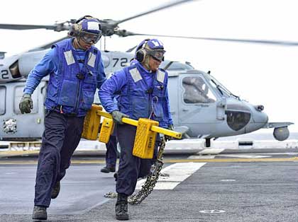 "SULU SEA (Aug. 9, 2018) Aviation Boatswain's Mate (Handling) Airman Detroit Brooks and Airman Taielua Lotoa remove chocks and chains from an MH-60S Sea Hawk helicopter, attached to the ""Blackjacks"" of Helicopter Sea Combat Squadron (HSC) 21, on the flight deck of Wasp-class amphibious assault ship USS Essex (LHD 2) during search and rescue operations for a missing Marine attached to the 13th Marine Expeditionary Unit (MEU). The Essex ARG/13th MEU is currently deployed to the 7th fleet area of operations. U.S. Navy photo by MC3 Jenna Dobson"